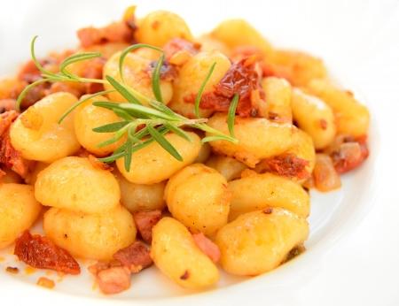 Gnocchi mit Tomaten, Speck und Zwiebeln auf dem wei�en Teller