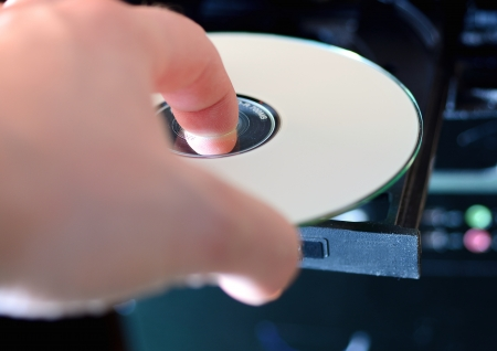 Hand puts the CD to the audio player  Archivio Fotografico