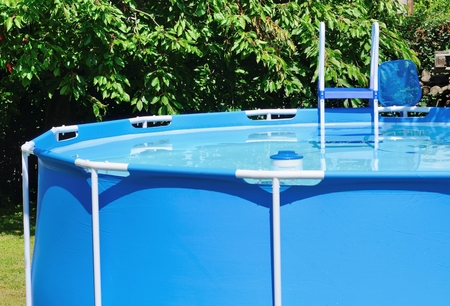 Circular water pool at garden with chlorine float and ladder