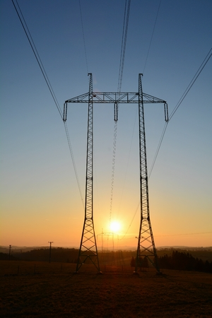 High voltage power lines with big and tall pylons during sunset. The sun sets between two pylons.