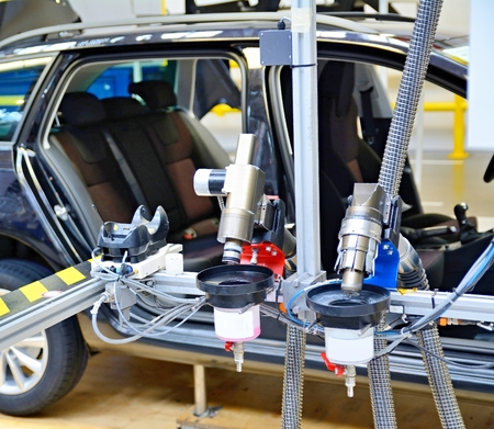 Closeup of the automated machine at assembly line in car factory. Stock Photo