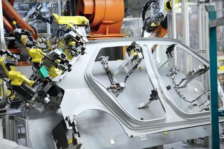 板金には、自動車工場の新しい車のためのパーツが刻印されています。ロボットは、新しい車のための部分を保持します。