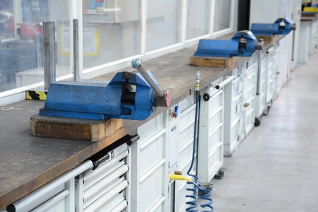 vice grip: Vice clamps on the bench in the factory hall.