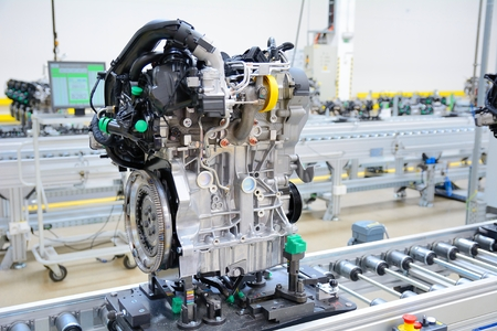 Newly manufactured engine on the production line in a factory. Behind the engine is computer on the desk.