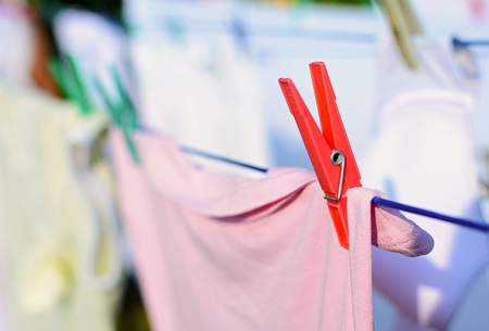 laundry line: Closeup of the red peg with fresh laundry on the clothesline. Stock Photo
