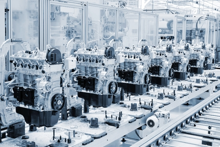 automotive industry: Manufactoring line with new engine parts. Photo is tone to cool blue color. Stock Photo