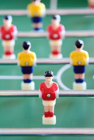 foosball: Closeup of the table football or foosball players in red and yellow jerseys.