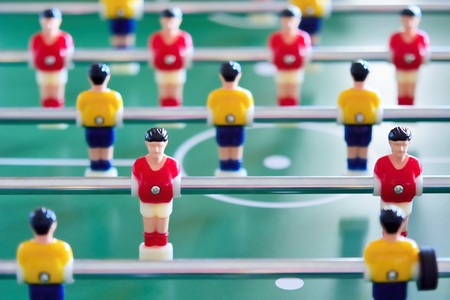 jerseys: Closeup of the table football or foosball players in red and yellow jerseys.