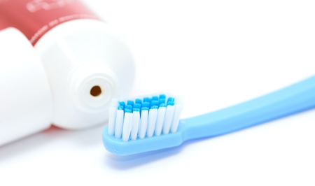 Blue toothbrush and tooth paste tube on white background. Closeup of the daily dental hygiene tool.