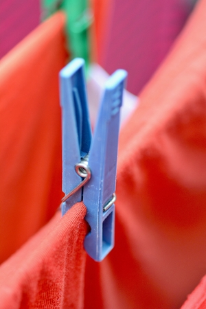 wet clothes: Clothespin on clothesline securing the red wet clothes. Red wet clothes drying on clothesline securing with clothespin.