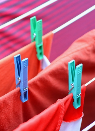 wet clothes: Clothespins on clothesline securing the red wet clothes. Red wet clothes drying on clothesline securing with clothespins.