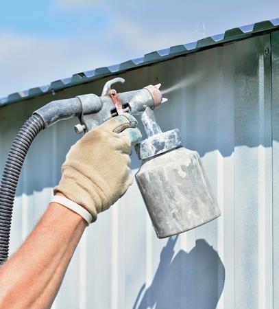 La pulverización de pintura blanca sobre una superficie galvanizada por un arma del aerógrafo.