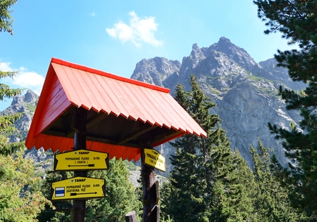 guidepost: POPRADSKE PLESO, SLOVAKIA - SEPTEMBER 12, 2016: Tourist guidepost near Popradske pleso lake in High Tatras with yellow direction signs with duration time of walk to the next guidepost.