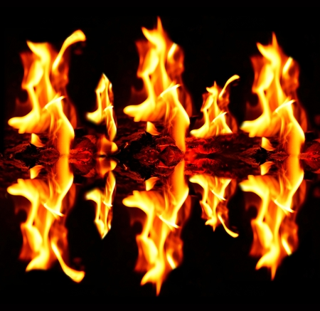 Blazing fire flames with reflection on dark black background.