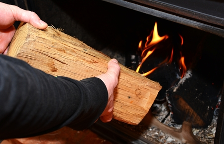 stoking: Man hands putting the log to the burning fireplace. Man stoking the wood into fireplace.