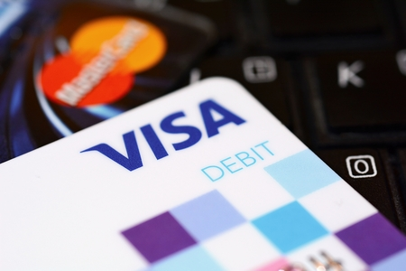 PRAGUE, CZECH REPUBLIC ? DECEMBER 12, 2016: VISA and MasterCard payment debit cards put on black keyboard. VISA and MasterCard provide multinational cashless and contactless payments worldwide.