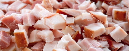 pancetta cubetti: Closeup background with chopped bacon cubes.