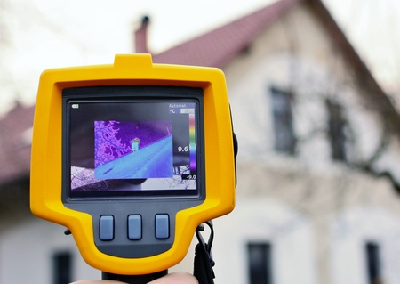 Recording Heat Loss of the Roof on the House with Infrared Thermal Camera in Hand.