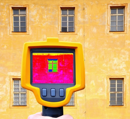thermography: An infrared thermal imager showing building facade and window heat loss. Stock Photo