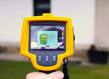 Recording Heat Loss of a House facade with Infrared Thermal Camera in Hand. Stock Photo