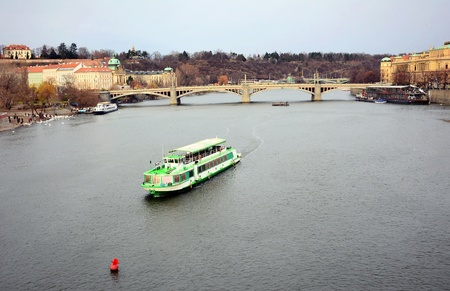View of the Vltava river with tourist ship and Prague Castle above in old Prague town center.