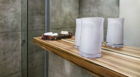 Bathroom wooden shelf with decorative candela glasses and soaps. 스톡 콘텐츠