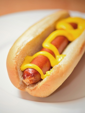 A cooked hot dog in a plain soft bun with mustard on a white plate. Stock Photo