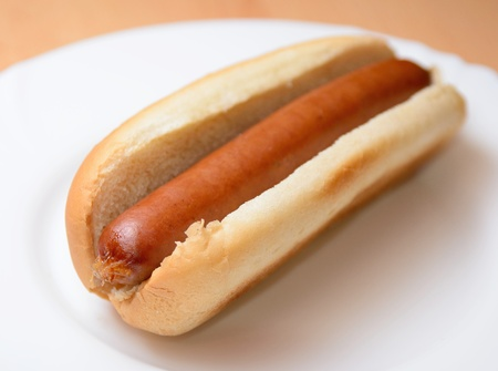 A cooked hot dog in a plain soft bun on a white plate.