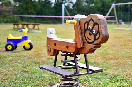 A close-up view of wooden swing on spring with plastic tricycle in the empty playground. Shallow depth of field. Focused on foreground.