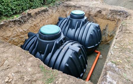 Dos tanques de almacenamiento subterráneos de plástico colocados bajo tierra para recolectar agua de lluvia. Foto de archivo