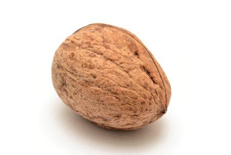 One whole walnut on white background.