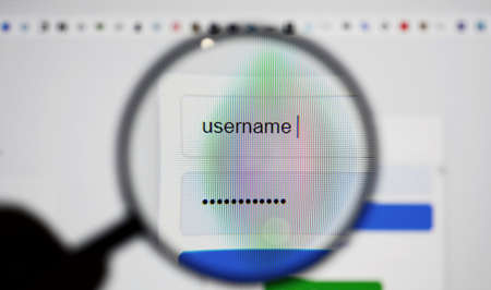 View through a magnifying glass on login page screen with username and password box in internet browser.