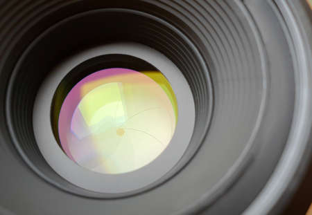 Closeup of aperture in camera lens with light reflection effect.