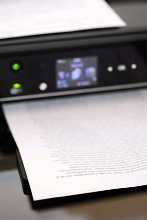 Printed paper with lorem ipsum text in modern inkjet printer. 스톡 콘텐츠