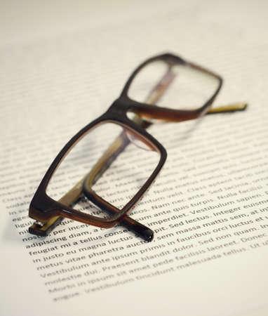 Closeup of folded eyeglasses on paper sheet with lorem ipsum text.
