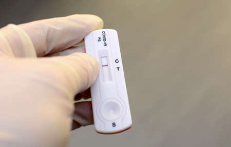 Hand in medical gloves is holding negative antigen rapid test for capturing of antibodies. It shows negative result.