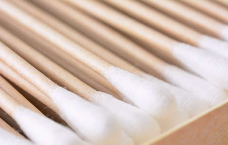 Closeup of the box full of ecological recyclable cleaning cotton swabs from recycled paper. It used for better environmental conservation. Cotton swabs on white background.