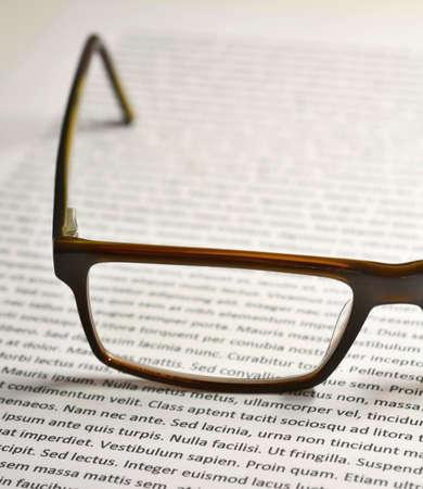 Closeup of eyeglasses on paper sheet with lorem ipsum text.