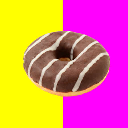 One whole chocolate donut isolated over half pink and half yellow background, retro vintage styled image. 스톡 콘텐츠