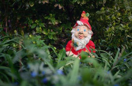 Vintage red ceramic gnome hidden behind the grass in the garden.