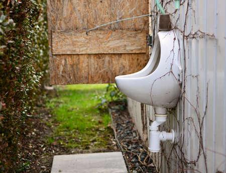 Outdoor vintage porcelain urinal in the backyard, garden.
