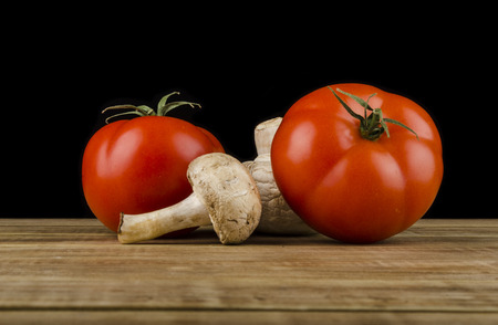 encurtidos: Tomatoes and mushroom , cooked on the old wooden table