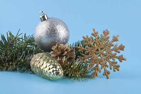 a branch of a Christmas tree and a Christmas tinsel on a blue background