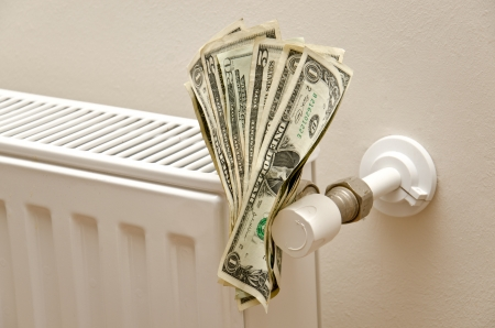 house warming: Money on a radiator  Expensive heating  Stock Photo