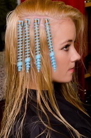 Blue curlers on the head in the hairdresser saloon  photo