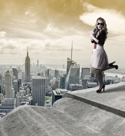 Pin-up woman watching New York City trough binoculars. photo