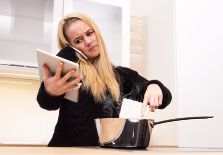 Young woman cooking from laptop, phone and tablet. photo