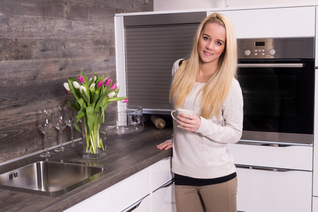 Young beautiful girl standing in the kitchen and drinks coffee photo
