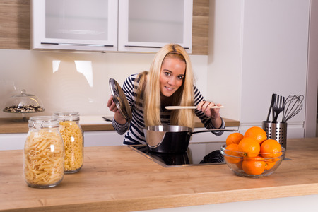 Cooking woman smelling the food in modern kitchen  photo