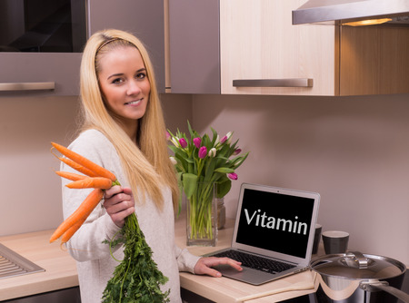 Woman with carrot and vitamin text on the laptop  photo